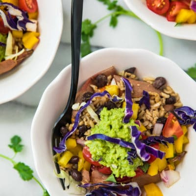 overhead view of Healthy Sweet Potato Burrito Bowls in white bowls with a black fork