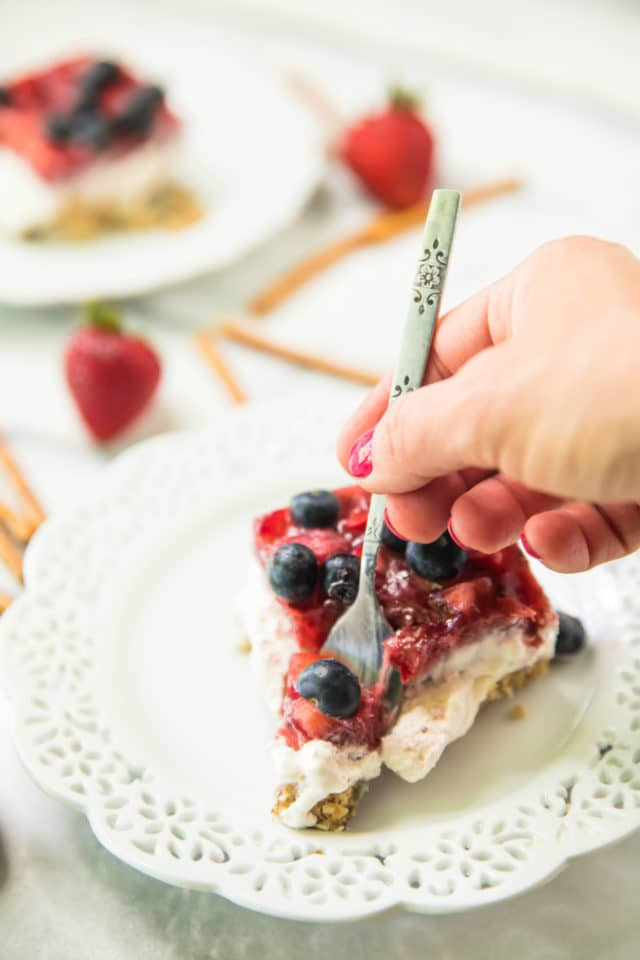 woman's hand using a fork to take a bite of Skinny Strawberry Pretzel Dessert