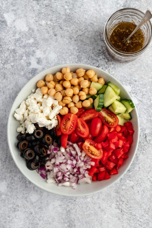 adding ingredients for a chickpea salad in a large white serving bowl