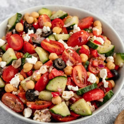 chickpea salad with tomatoes and cucumber in a large white serving bowl