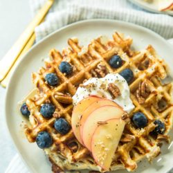 healthy protein waffle recipe topped with sliced apples, Greek yogurt and blueberries