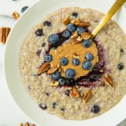 oatmeal in a white bowl topped with blueberries, almond butter, pecans and blueberry jam