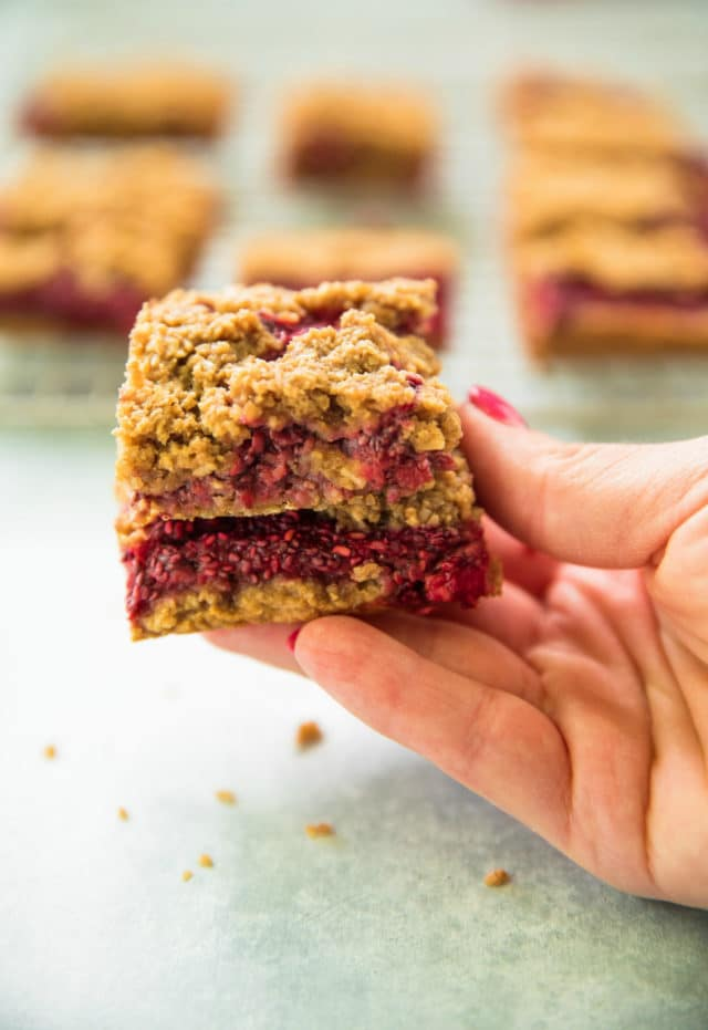 woman's hand holding Raspberry Almond Oat Bars