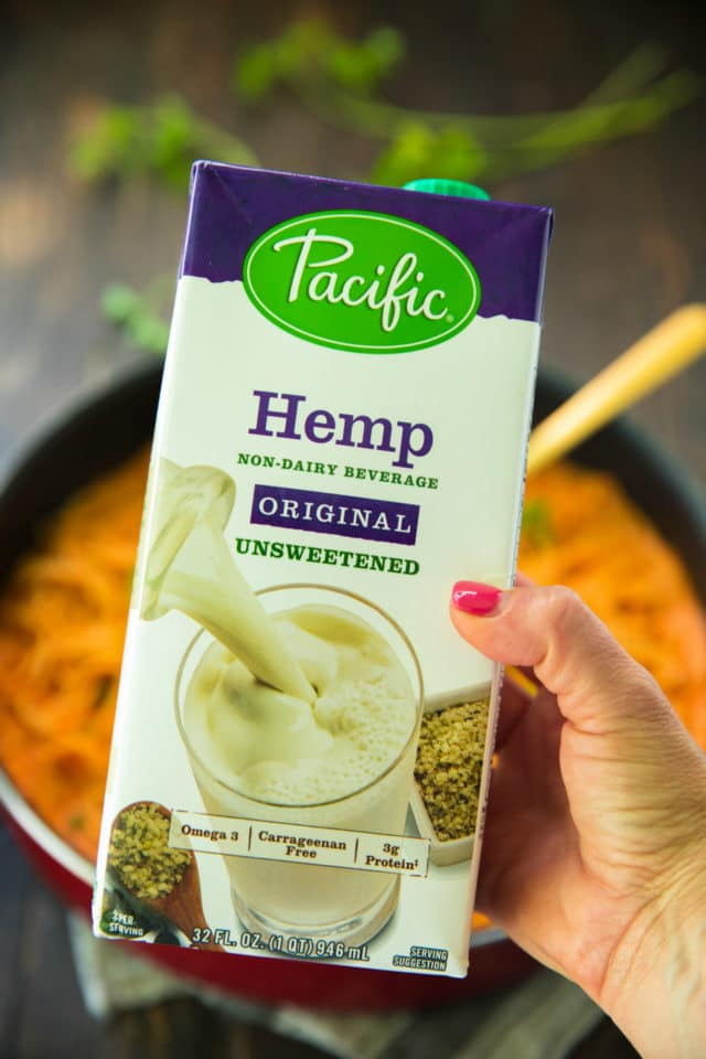 woman's hand holding Hemp Plant-Based Beverage used to make Vegan Roasted Red Pepper Pasta Sauce