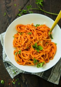 Vegan Roasted Red Pepper Pasta Sauce over pasta in a white bowl with gold fork