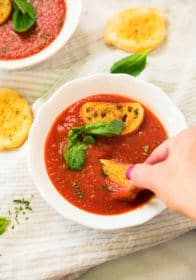 overhead view of woman's hand dipping garlic bread into Healthy Roasted Tomato Basil Soup