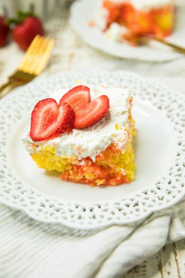 a piece of Easy Strawberry Lemonade Poke Cake on a white plate with two strawberry slices on top