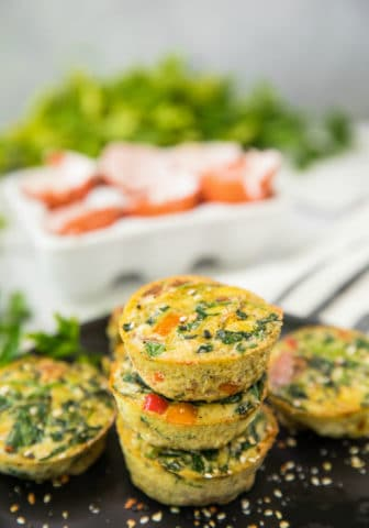 Healthy Sweet Potato Spinach Egg Cups stacked on a black plate