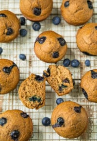 Healthy Blueberry Banana Muffins on a cooling rack with blueberries