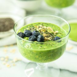 Matcha Collagen Overnight Oats in a glass, topped with oats, blueberries and chia seeds