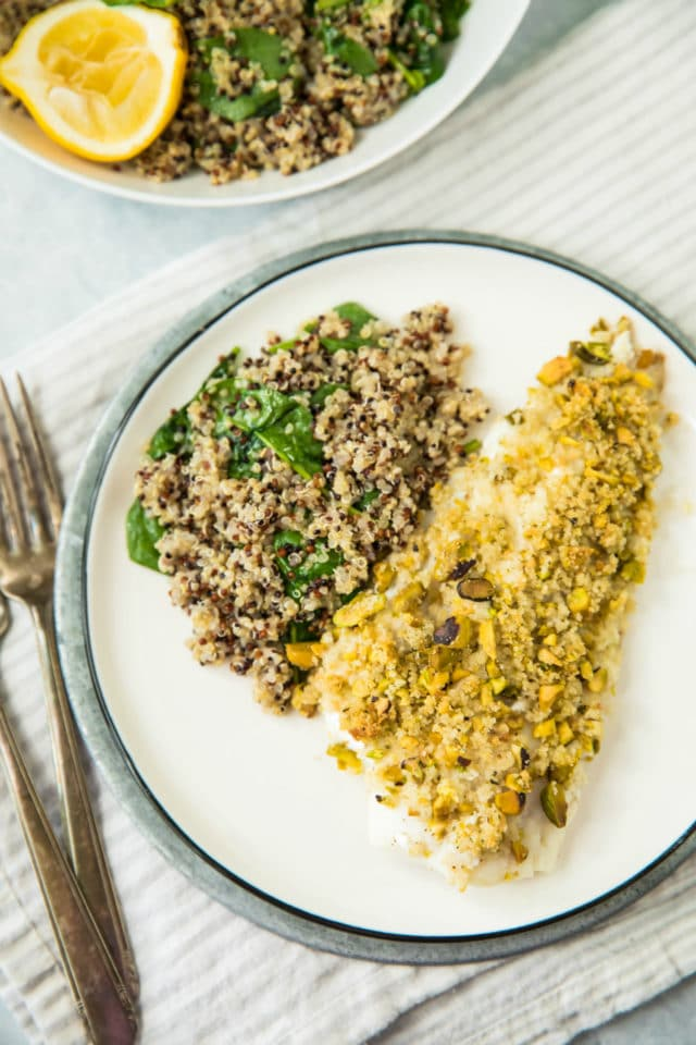 Healthy Pistachio Crusted White Fish served with quinoa on a white plate