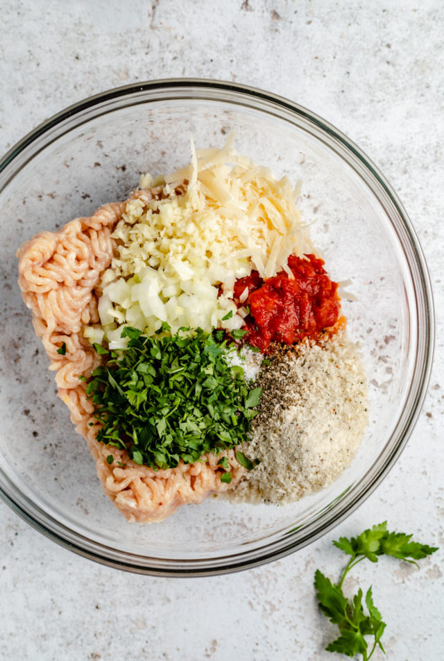 mixing ground chicken with ingredients for chicken burgers