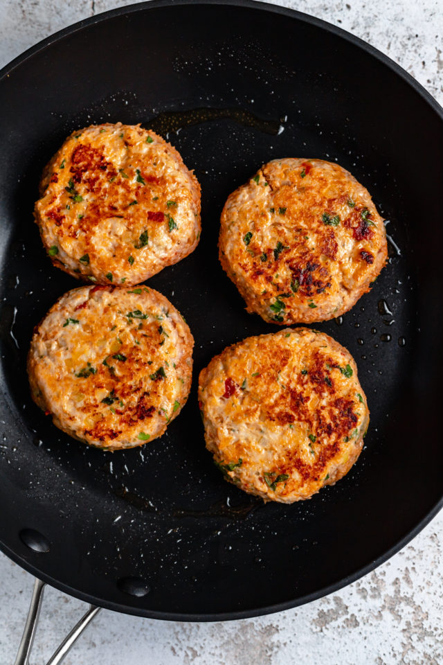 chicken burgers cooking in a large skillet