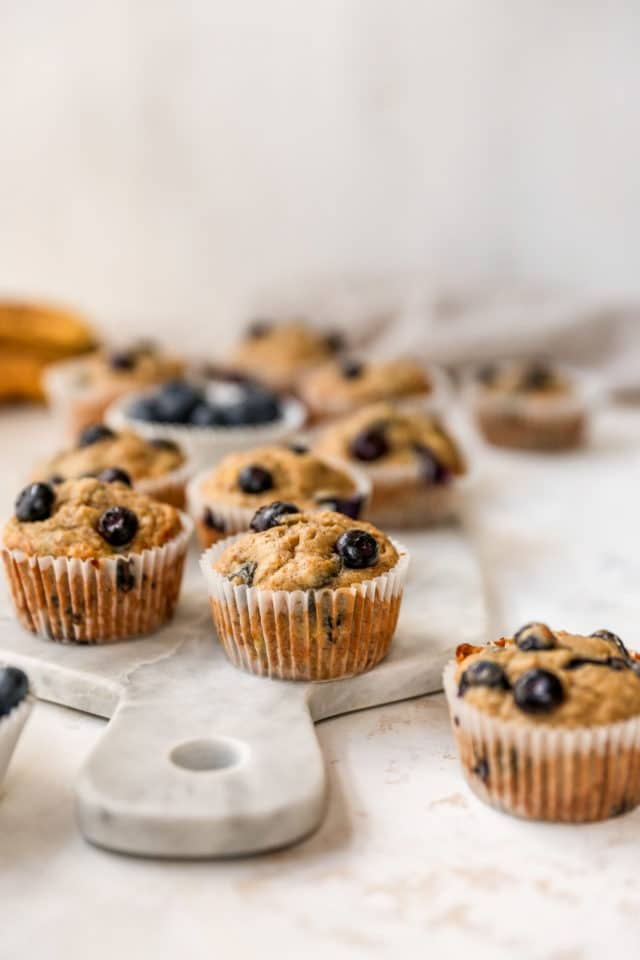 blueberry muffins in a cupcake liner sitting on a marble cutting board