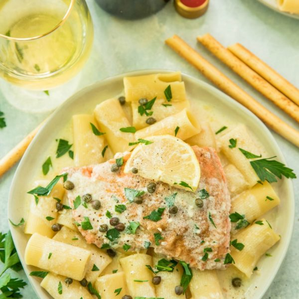 overhead view of Creamy Salmon Piccata served over pasta with wine and breadsticks