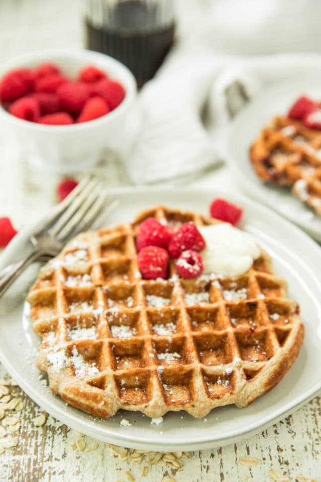 side view of Healthy Raspberry Banana Oatmeal Greek Yogurt Waffles on white plates with a small white bowl of red raspberries