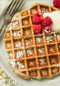 close view of Healthy Raspberry Banana Oatmeal Greek Yogurt Waffles topped with yogurt and raspberries