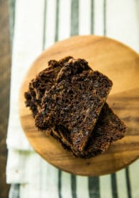 overhead view of stacked slices of Healthy Double Chocolate Zucchini Bread on a round wooden board