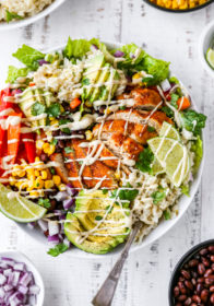 burrito bowls topped with chicken, avocado and dressing