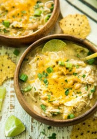 overhead image of Gut-Healing Easy Slow Cooker White Chicken Chili served in a wooden bowl with a gold spoon
