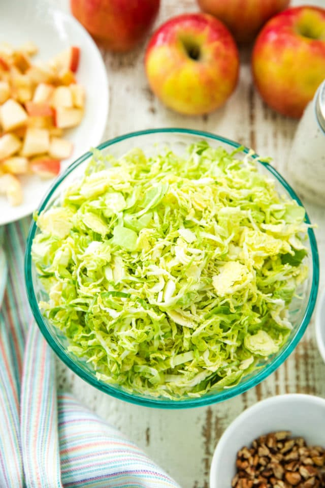 overhead of shredded Brussels sprouts in a glass bowl for the Autumn Shredded Brussels Sprouts Apple Salad