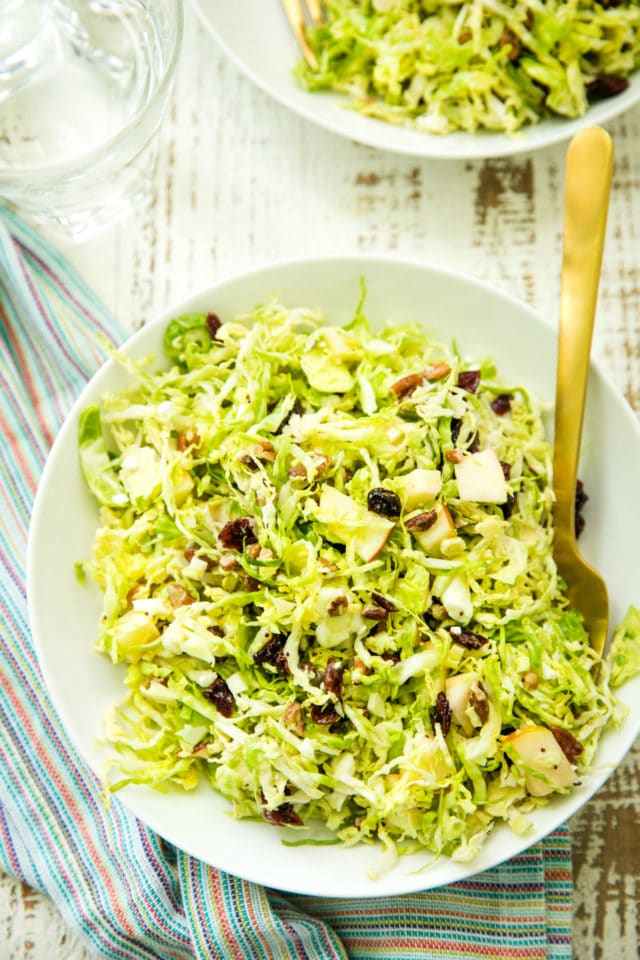overhead view of a Autumn Shredded Brussels Sprouts Apple Salad in a white bowl with a gold fork
