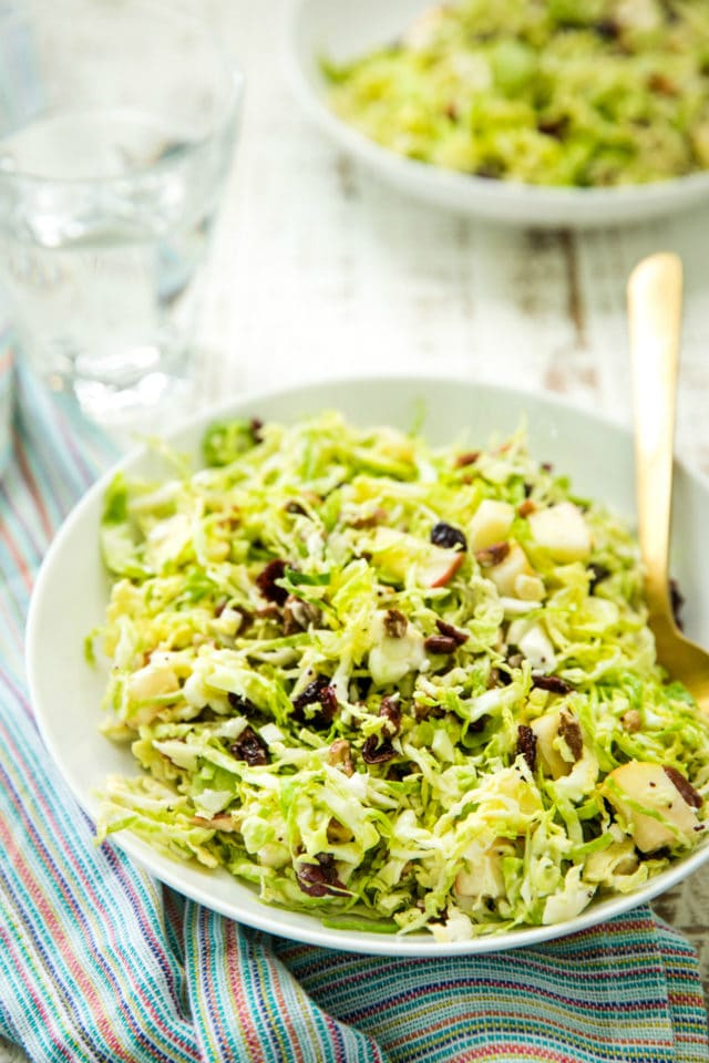 Side view of Autumn Shredded Brussels Sprouts Apple Salad in a white bowl with a gold fork