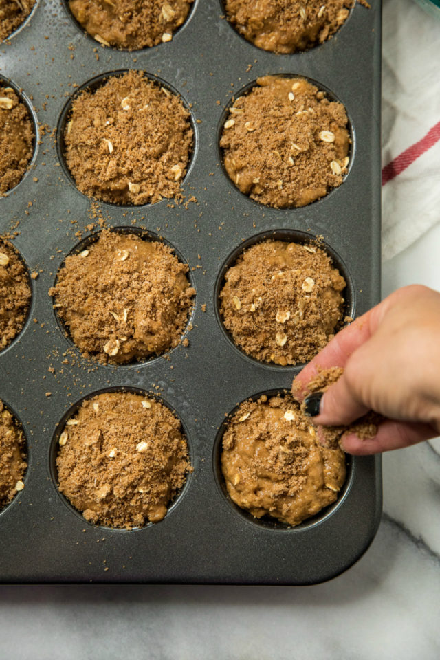 a woman's hand adding the topping to the Healthy Apple Spice Crumb Muffins