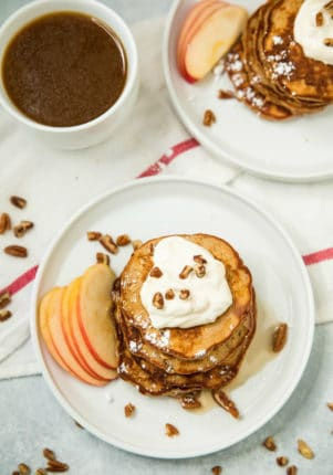 overhead photo of Apple Cinnamon Protein Pancakes on white plates, served with a cup of coffee
