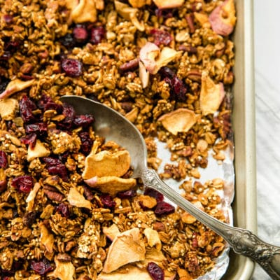 granola on a baking pan with a large silver spoon