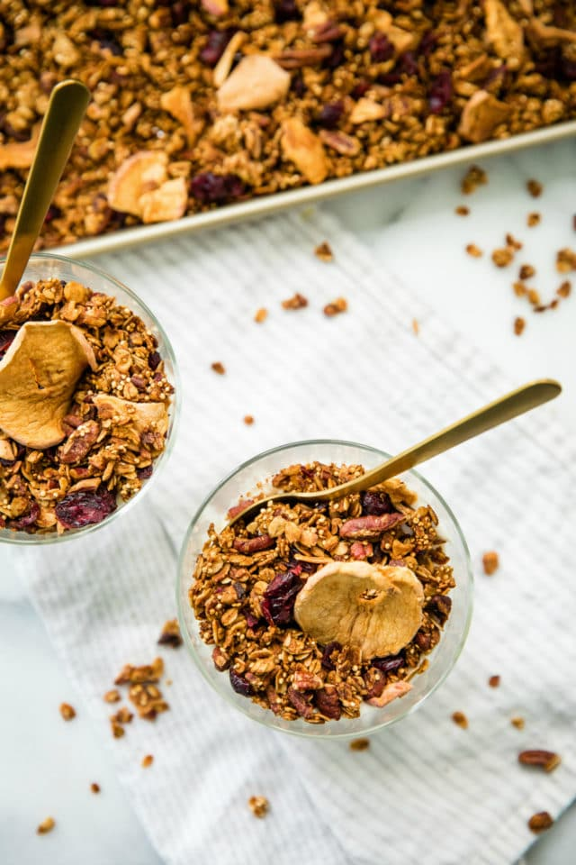 overhead photo of Apple Pecan Quinoa Granola in glasses with gold spoons