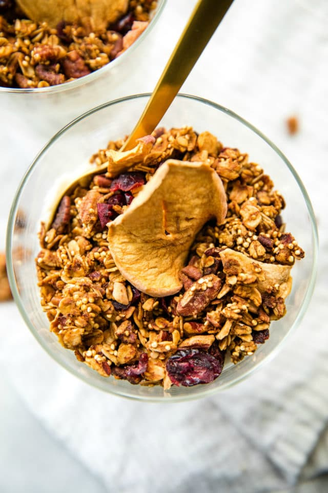 overhead close up photo of a glass full of Apple Pecan Quinoa Granola with a gold spoon