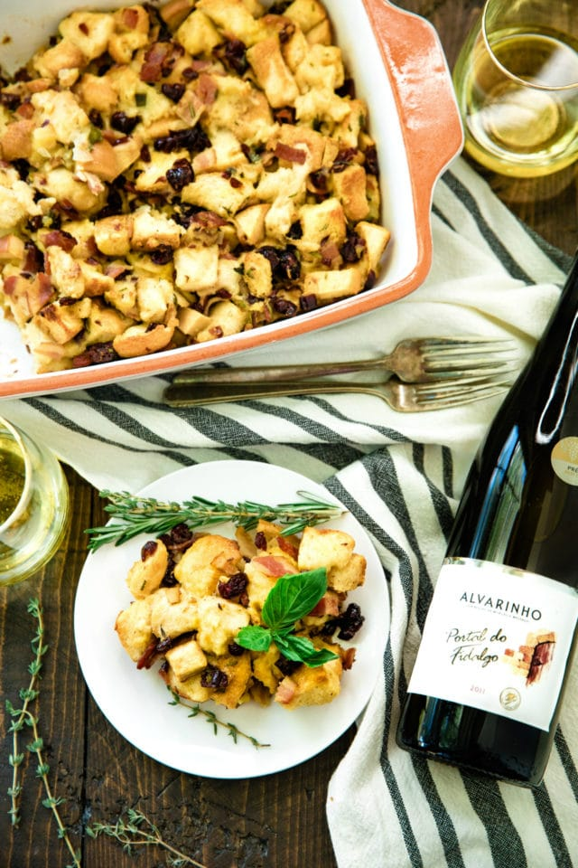 Easy Bacon Apple Stuffing Recipe served on a white plate with a glass of wine on the side
