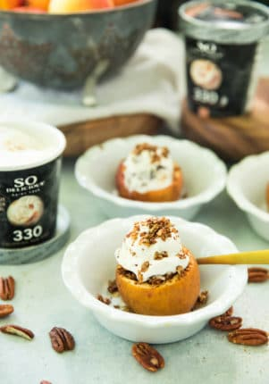 Healthy Apple Crisp Stuffed Baked Apples topped with a scoop of ice cream in small white bowls with gold spoons