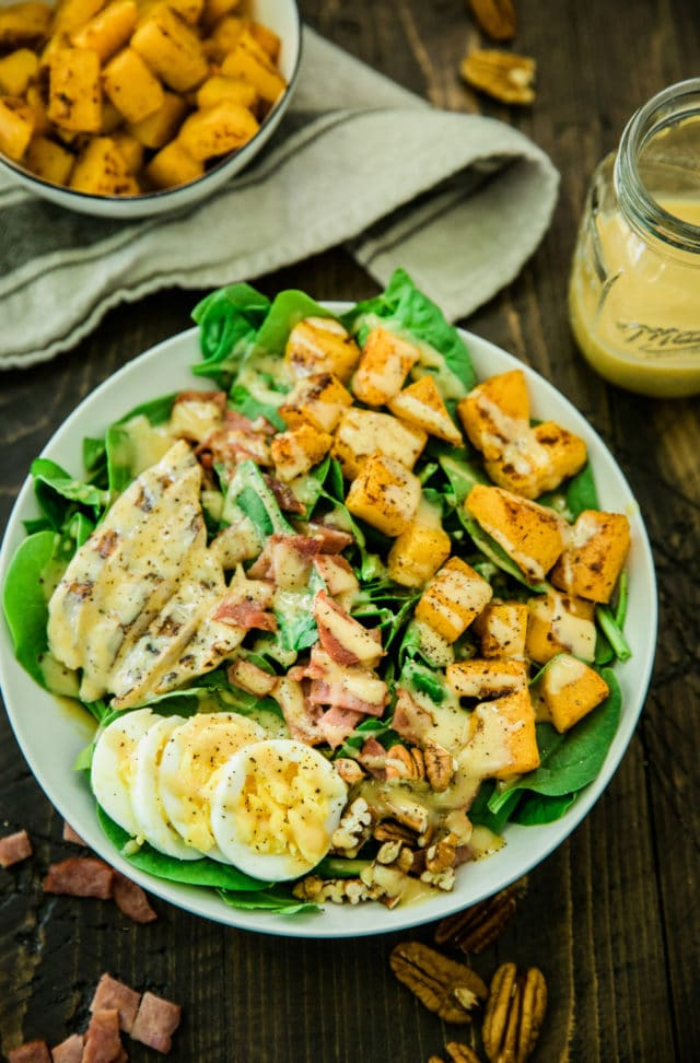 overhead photo of the Healthy Harvest Cobb Salad served in a white bowl with a side of dressing in a glass jar