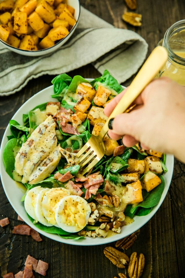 overhead view of woman's hand holding a gold fork over the Healthy Harvest Cobb Salad