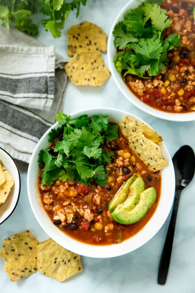 overhead of healthy taco soup served in a white bowl topped with avocado slices, chips and cilantro