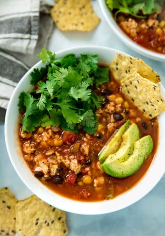 closeup overhead of healthy taco soup served in a white bowl topped with avocado slices, chips and cilantro