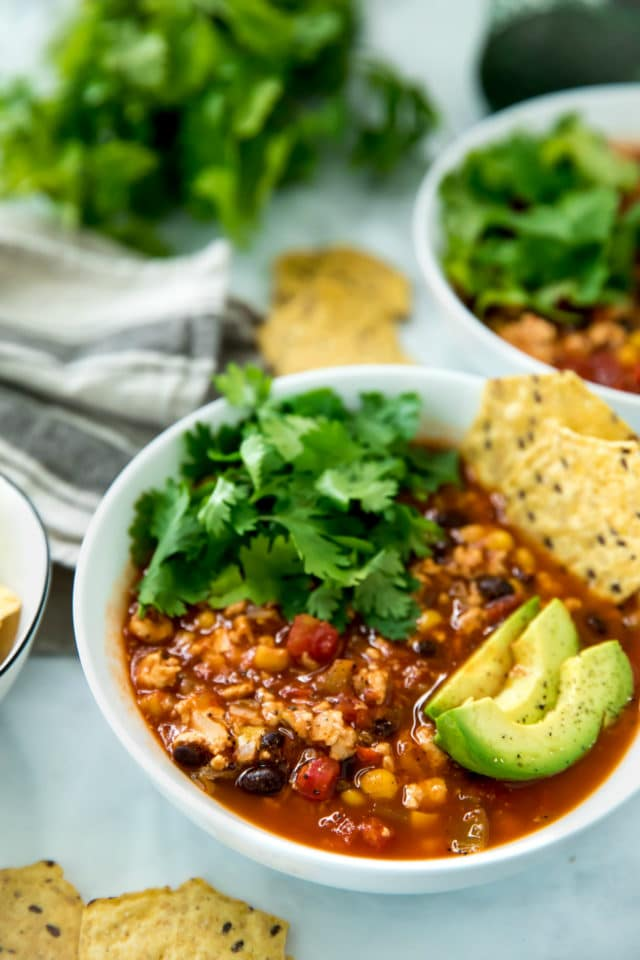 closeup side view of healthy taco soup served in a white bowl topped with avocado slices, chips and cilantro