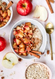 bowl of oatmeal topped with apple and pecans