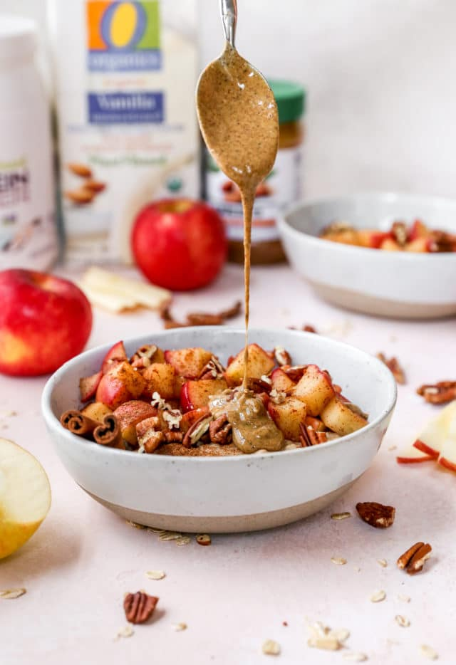 drizzling almond butter over apple cinnamon oatmeal
