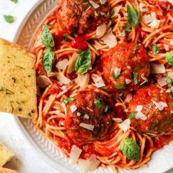 spaghetti and meatballs served with garlic and bread and topped with fresh basil