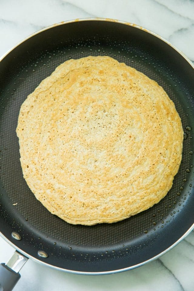 cooking the Homemade Oat Flour Pizza Crust in a skillet