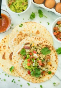 overhead image of a Healthy Breakfast Burrito Recipe on a white marble surface served with salsa pico and de Gallo