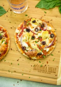 overhead photo of Easy Greek Pita Pizzas Recipe on a wooden cutting board