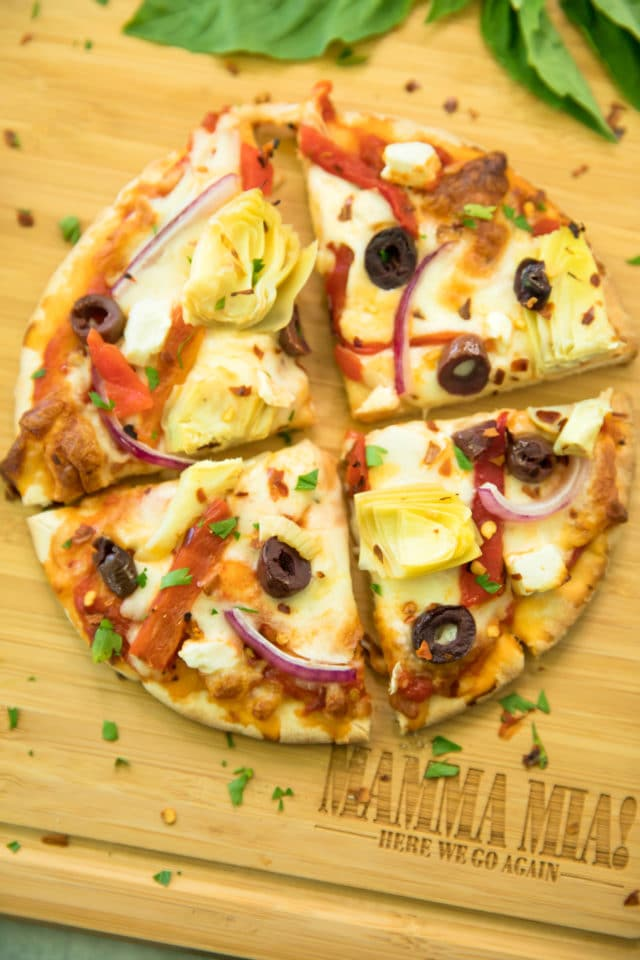 overhead closeup photo of Easy Greek Pita Pizzas Recipe sliced over a wooden cutting board