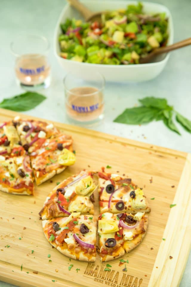 Easy Greek Pita Pizzas Recipe on a wooden cutting board with a salad on the side