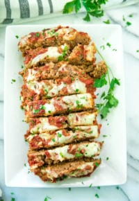 overhead image of Cheesy Italian Meatloaf Recipe sliced on a white serving platter