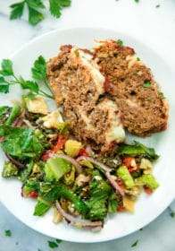 closeup overhead image of slices of Cheesy Italian Meatloaf Recipe on a white plate with a side salad