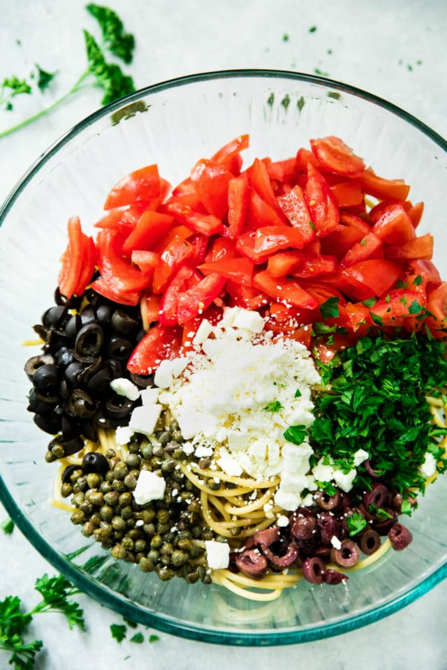 overhead closeup image of the ingredients for the Easy Greek Pasta Salad in a glass bowl